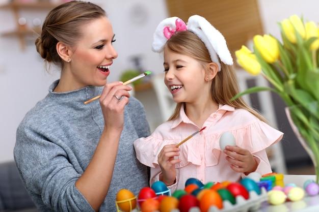 Madre e figlia che dipingono le uova di pasqua a casa