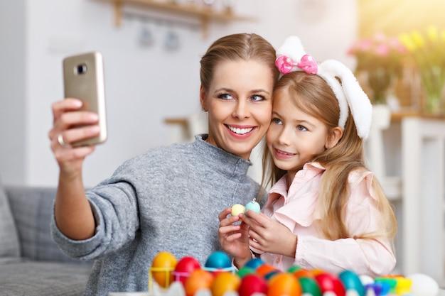 Madre e figlia che dipingono le uova di pasqua e si fanno selfie