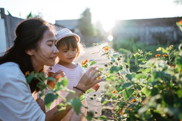 Madre e figlia che raccolgono fiori piuttosto colorati nel parco