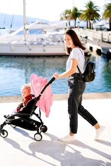 Madre e figlia in un passeggino pinl che camminano in un porto turistico.