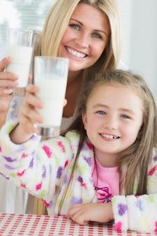 Madre e figlia che alza gli occhiali per il latte