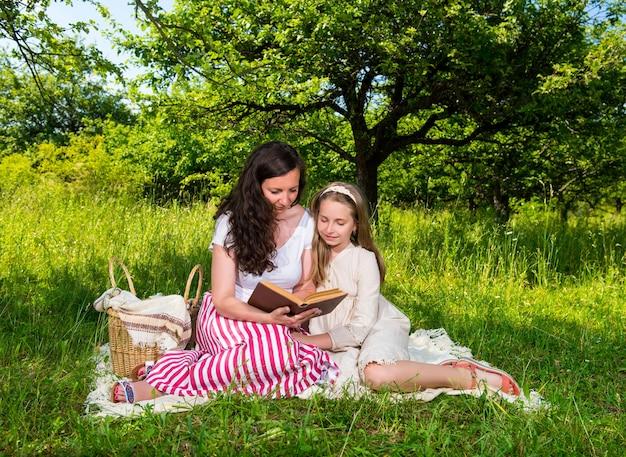 Madre e figlia che leggono un libro nel parco. tempo per la famiglia
