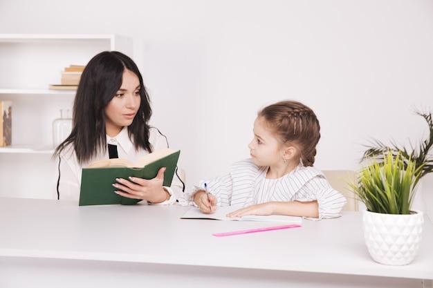 Tempo di lettura di madre e figlia. imparare insieme seduti a tavola.