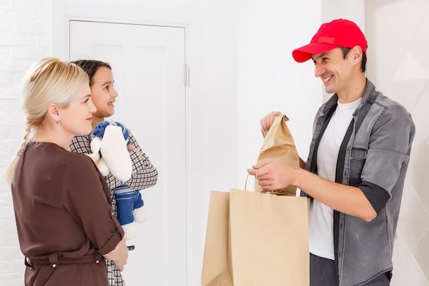 Madre e figlia ricevono l'ordine dal fattorino, consegna di giocattoli e merci per bambini a casa