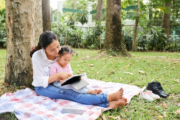 Madre e figlia che riposano sotto l'albero
