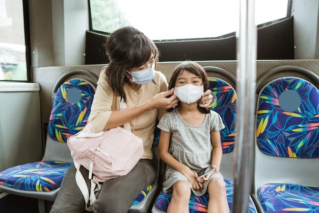 Madre e figlia che guidano i mezzi pubblici durante la pandemia che indossa la maschera facciale