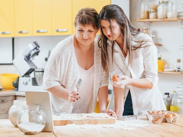 Madre e figlia che girano video di cucina su tablet per il loro blog culinario