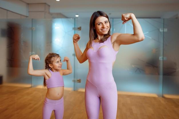 Madre e figlia mostra i muscoli in palestra, stile di vita sano, allenamento fitness. mamma e bambina in abiti sportivi, donna con bambino in formazione congiunta in club sportivo