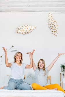 Madre e figlia si siedono sul letto e gettano i cuscini verso l'alto, gioia e divertimento, comunicazione, famiglia, stile, mattina
