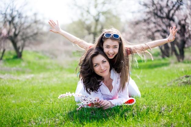 Madre e figlia si siedono sull'erba nel parco