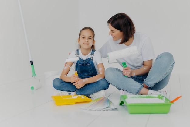 La madre e la figlia si siedono insieme sul pavimento