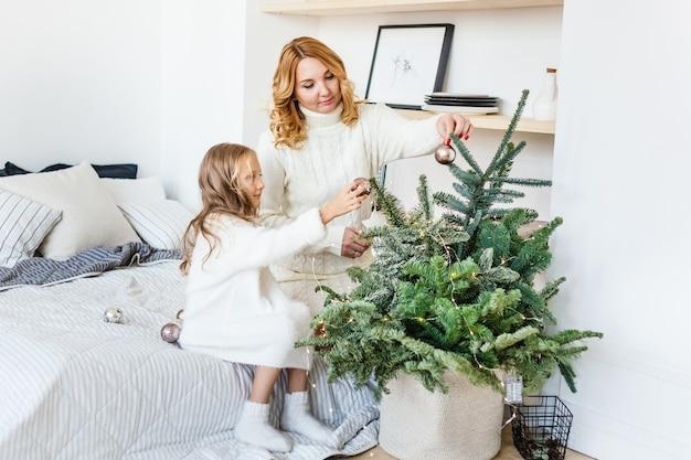 Madre e figlia che si siedono sul letto a casa che decorano per capodanno e natale