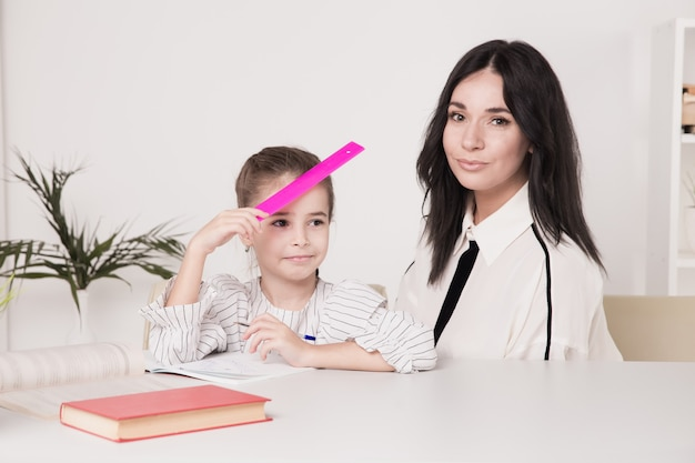 Madre e figlia sedute alla scrivania a fare i compiti insieme.