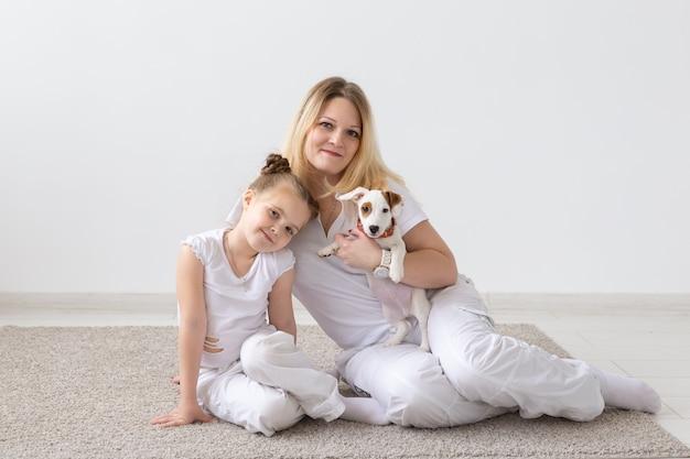 Madre e figlia che si siedono sul pavimento con il cucciolo jack russell