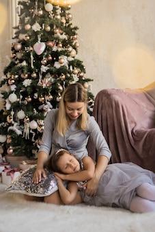 Madre e figlia che si siedono e che si abbracciano sullo sfondo dell'albero di natale