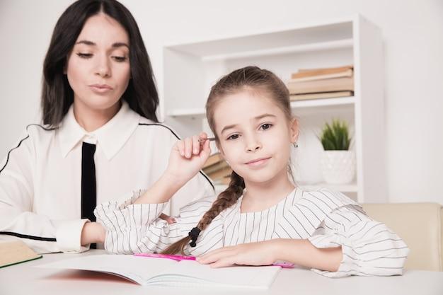 Madre e figlia seduti al tavolo e fare i compiti insieme a casa.