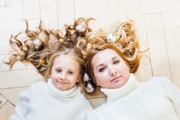 Madre e figlia che si siedono con gli ornamenti di natale