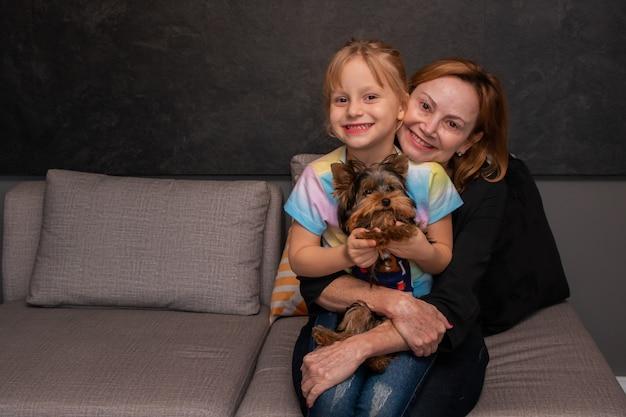 Madre e figlia sul divano in soggiorno che abbracciano il loro cane. festa della mamma