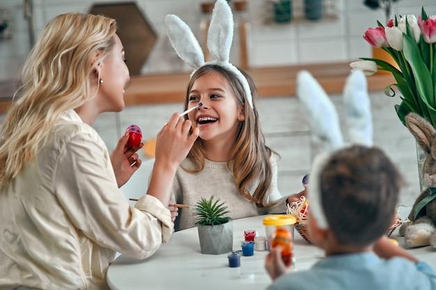 Una madre, una figlia e un figlio che celebrano la pasqua, dipingendo le uova con il pennello. famiglia felice che sorride e che ride, attingendo alla faccia. bambina sveglia nelle orecchie del coniglietto che prepara la vacanza.