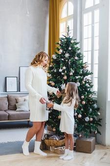 Madre e figlia stanno vicino all'albero di natale, decorano l'albero di natale, capelli chiari e maglioni bianchi, bellissime decorazioni, atmosfera natalizia
