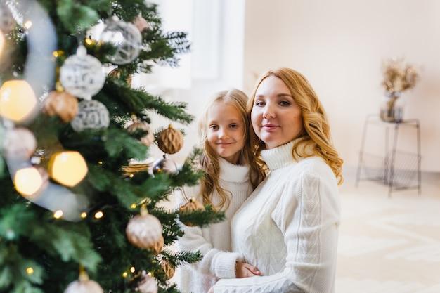 Madre e figlia in piedi vicino all'albero di natale
