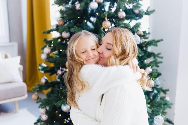 Madre e figlia in piedi vicino all'albero di natale Foto Premium