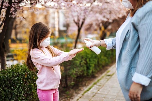 Madre e figlia in piedi nel parco, indossano maschere protettive e disinfettano le mani con l'alcol.