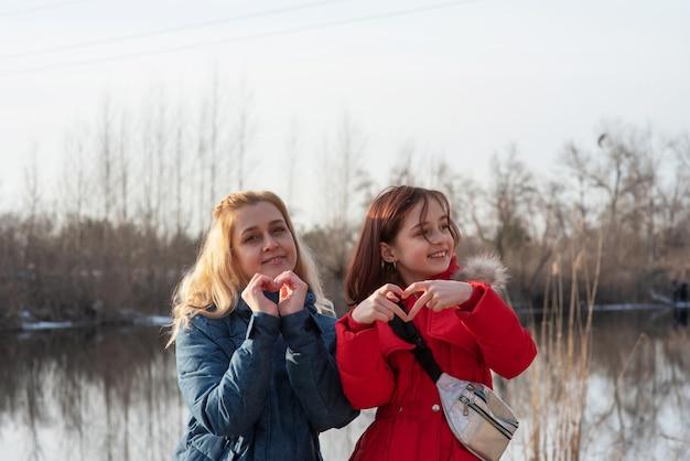 Una madre e una figlia in piedi nella giornata invernale. mamma e figlia in giacche in natura in riva al fiume.