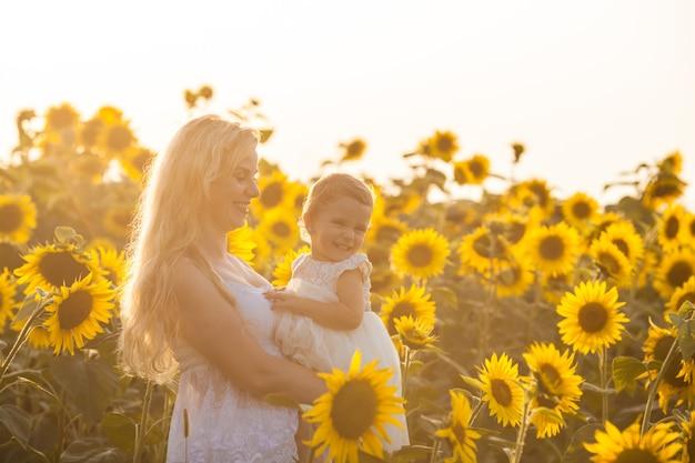 Madre e figlia in un campo di girasoli come regina e principessa dei campi