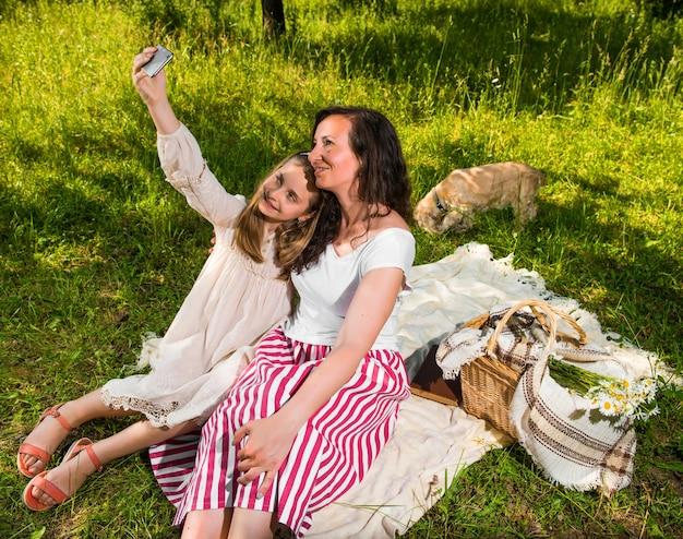 Madre e figlia che prendono un selfie nel parco