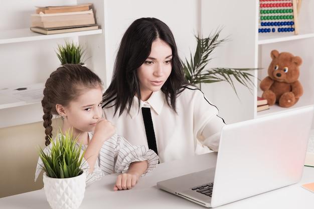 Madre e figlia che utilizzano computer portatile e internet insieme a casa.