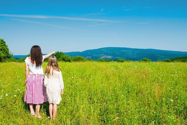 Madre e figlia che camminano nel parco. madre che indica