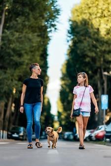 Madre e figlia che camminano per la strada con un cane