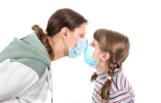 Madre e figlia che indossano una maschera per il viso del virus che baciano il concetto per il virus corona