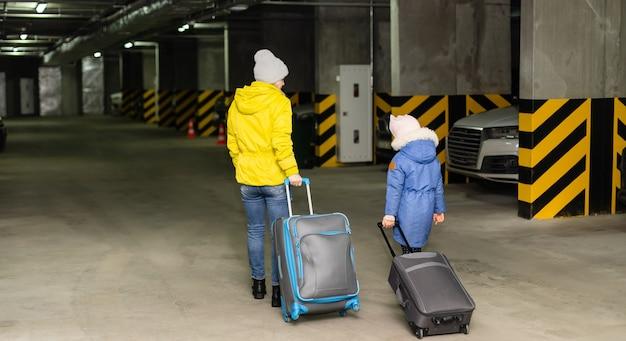 Madre e figlia con borsa in un garage sotterraneo pubblico.