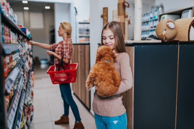 Madre e figlia con il loro cucciolo di barboncino in un negozio di animali.
