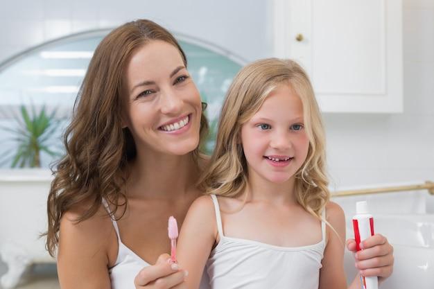 Madre e figlia con spazzolino e dentifricio