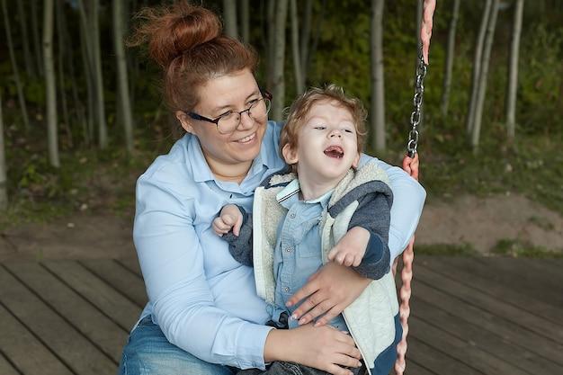 Madre e figlio disabile camminano all'aria aperta su una sedia, madre e bambino sorridono