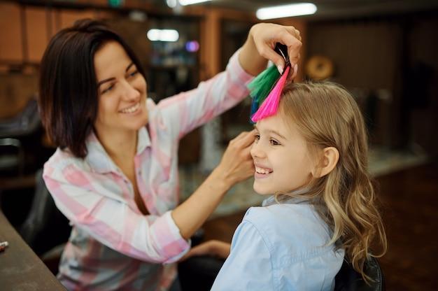 Madre che fa acconciatura al suo bambino nel salone di parrucchiere