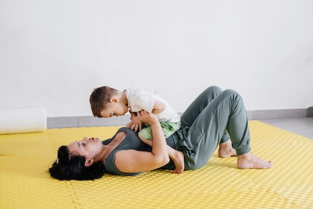 Madre che fa esercizi fisici giocando con un ragazzo disabile