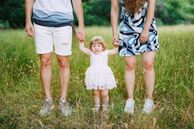 Madre e padre tengono la figlia per le braccia.