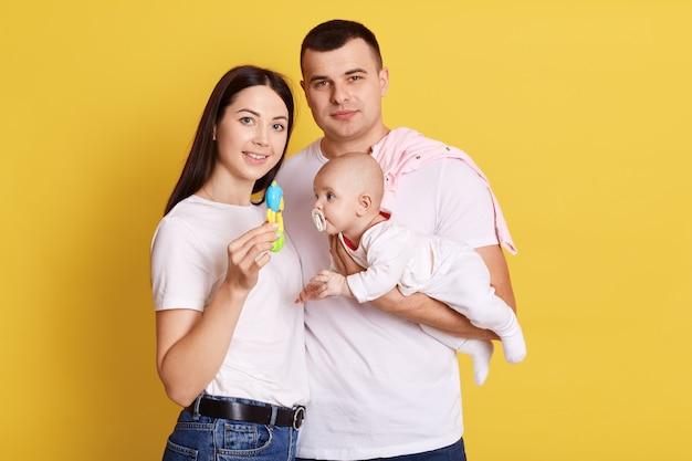 Madre, padre e bambino in posa isolata sopra la parete gialla, mamma con il sacco in mano, famiglia che indossa magliette bianche casual. genitori felici con la loro figlia neonata.
