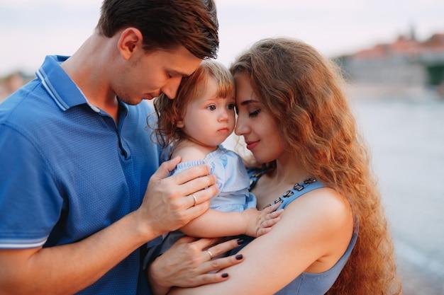 Madre e padre tengono delicatamente la loro figlia tra le braccia.