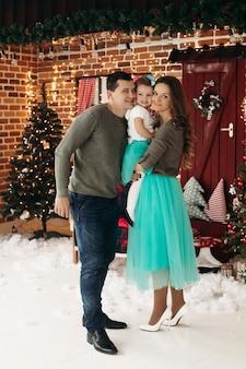 Madre e padre che tengono la figlia nelle mani e baciano le sue guance Foto Premium