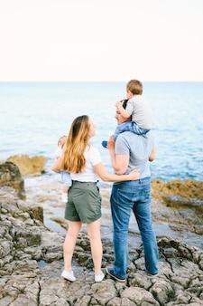 Madre e padre che tengono i loro figli pur avendo una giornata con la famiglia sulla spiaggia rocciosa