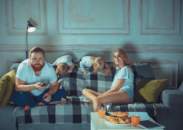 Madre, padre e figli a casa si divertono, il comfort e il concetto di amore accogliente sembrano felici