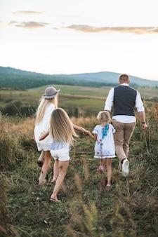 Madre e padre che giocano con le figlie dei loro bambini nel campo