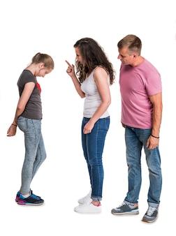 Madre e padre che gridano alla figlia adolescente su un muro bianco