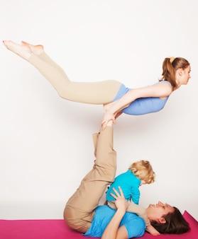 Madre, padre e figlio che fanno yoga su sfondo bianco
