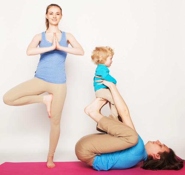 Madre, padre e figlio che fanno yoga su sfondo bianco Foto Premium